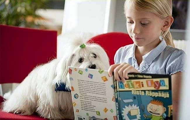Chú chó lắng nghe trẻ đọc sách